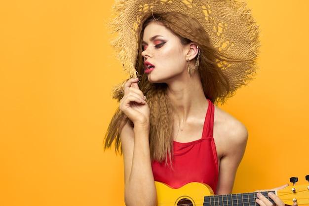 Vrouw in rode jurk hoed ukelele dragen in handen