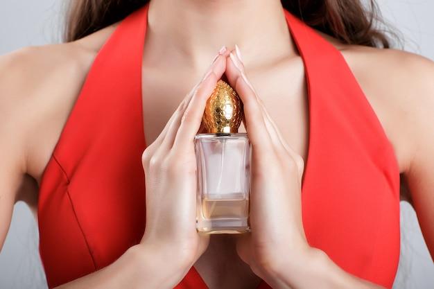Vrouw in rode jurk houdt een mooie parfumfles vast