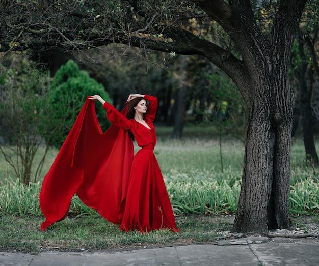 Vrouw in rode jurk in de natuur poseren.