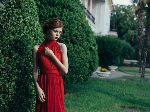 Vrouw in rode jurk luxe charme lopen groene bush natuur gotische zomer