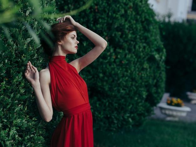 Vrouw in rode jurk luxe prinses maskerade charme groene bladeren.