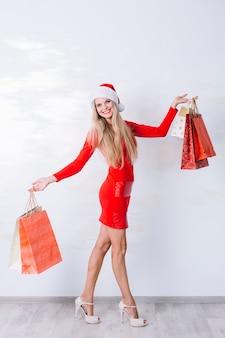 Vrouw in rode jurk met boodschappentassen in handen