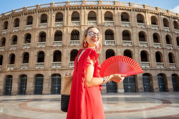 Vrouw in rode jurk met spaanse handventilator die terug staat voor het amfitheater van de arena in de stad valencia, spanje