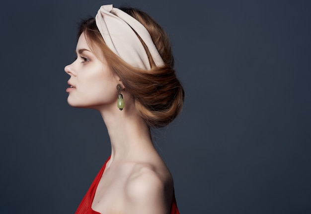 Vrouw in rode jurk oorbellen hoofdband mode elegante stijl