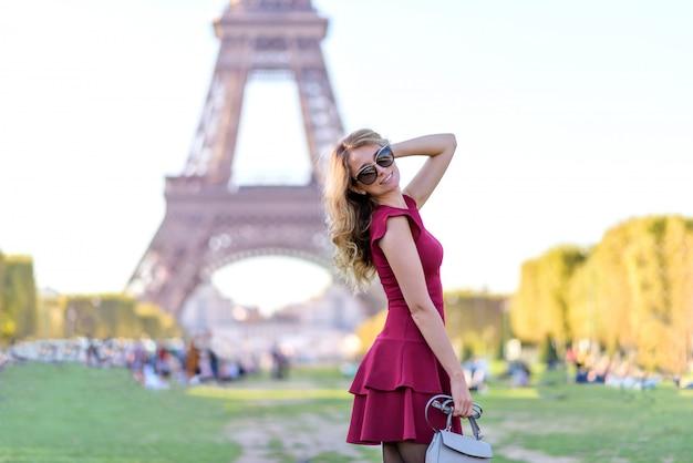 Vrouw in rode jurk op de eiffeltoren in frankrijk