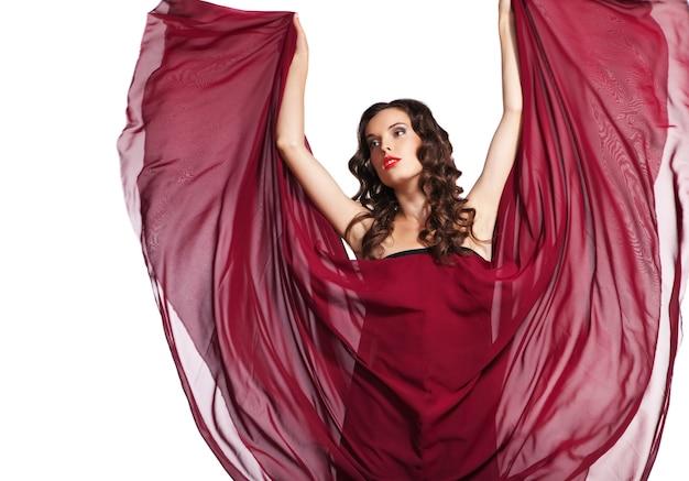 Vrouw in rode jurk vliegen op wind geïsoleerd