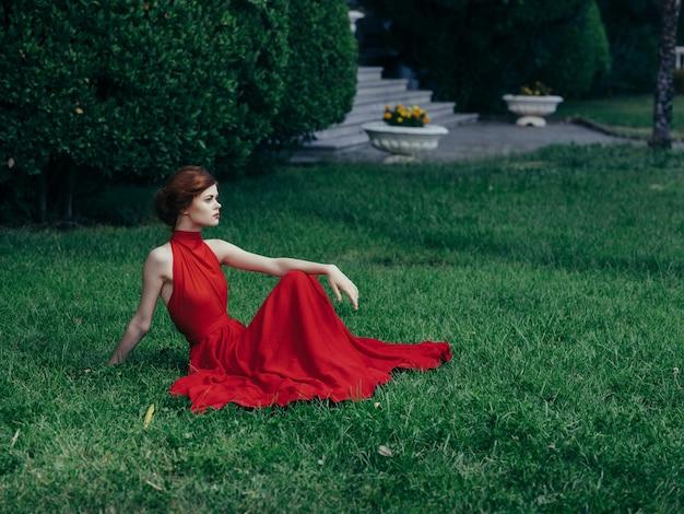 Vrouw in rode jurk zittend op het gazon in de tuin fantasie decoratie