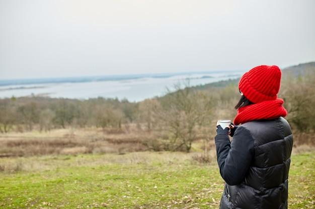 Vrouw in rode muts en sjaal, thee drinken uit metalen beker buiten, travel concept, herfst achtergrond landschap.