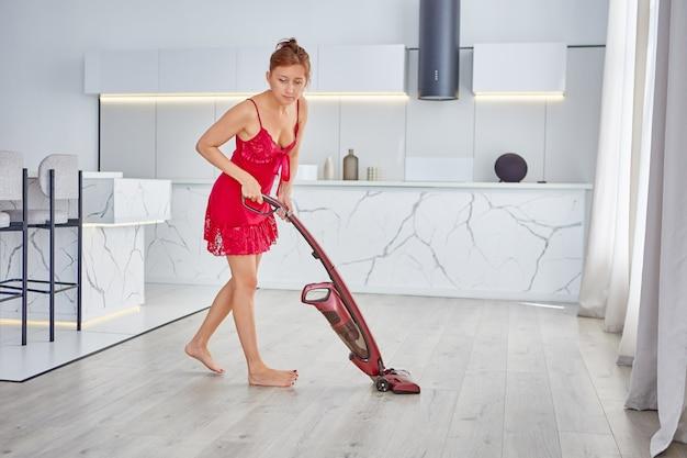 Vrouw in rode peignoir stofzuigt vloer met draadloze stofzuiger