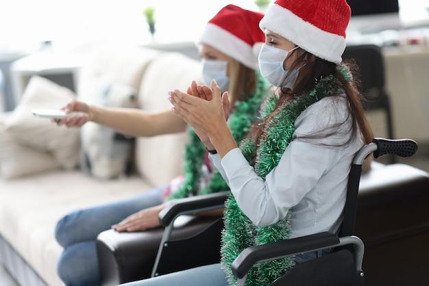 Vrouw in rode pet en sieraden om haar nek in rolstoel en gezichtsschild klapt handen met haar vriend met tv-afstandsbediening