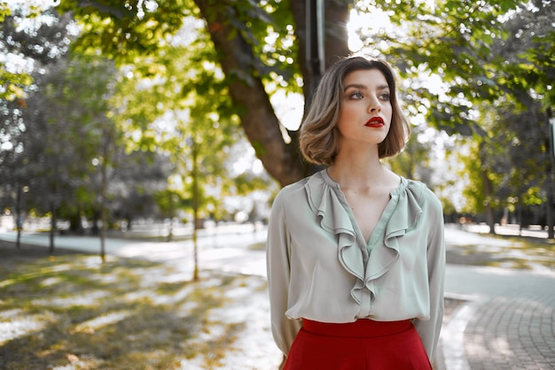 Vrouw in rode rok loopt in de levensstijl van parkbomen