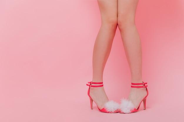 Vrouw in rode sandalen op hakken staat op roze muur