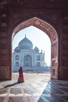 Vrouw in rode saree / sari in taj mahal, agra, uttar pradesh, india