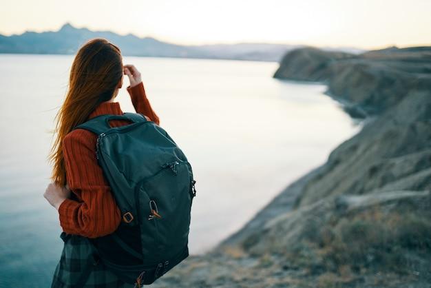 Vrouw in rode sweater met rugzak en de overzeese bergen van het reistoerisme