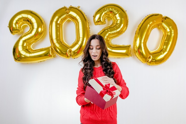 Vrouw in rode sweater openingskerstmis huidig voor 2020 nieuwe jaarballons
