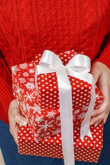 Vrouw in rode trui bedrijf presenteert in handen close-up