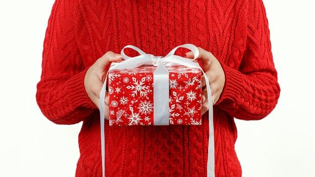 Vrouw in rode trui cadeau in handen houden