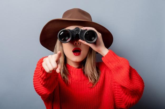 Vrouw in rode trui en hoed met verrekijker