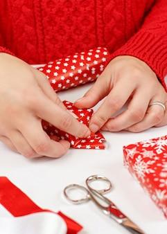 Vrouw in rode trui inwikkeling aanwezig in een rood papier close-up