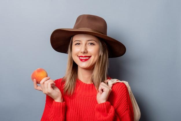 Vrouw in rode trui met perzik en tas