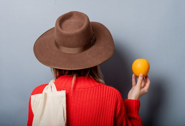 Vrouw in rode trui met sinaasappel en tas