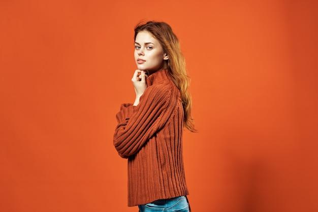 Vrouw in rode trui mode studio poseren rode achtergrond