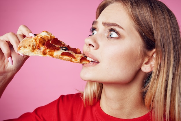 Vrouw in rode tshirt snack fastfood roze achtergrond