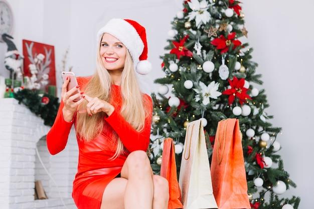 Vrouw in rode zitting met telefoon dichtbij kerstboom