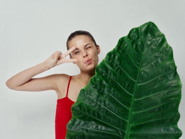 Vrouw in rode zwembroek palmblad emoties handgebaar lichte achtergrond