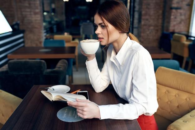 Vrouw in rokoverhemd aan lijst in koffiekoffiekop ter beschikking en kladblok-pen