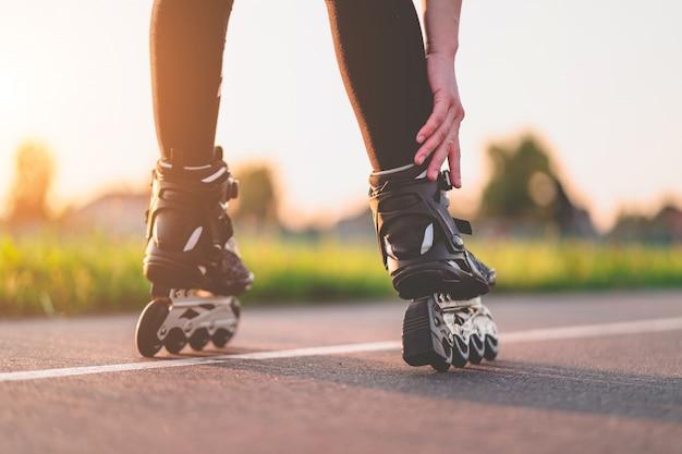 Vrouw in rolschaatsen tijdens inline skaten buitenshuis. actieve levensstijl. tiener tijdens skaten