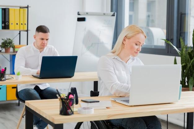 Vrouw in rolstoel die bij haar bureau werkt