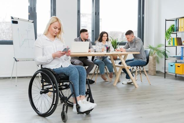 Vrouw in rolstoel die van haar telefoon op het kantoor werken