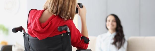 Vrouw in rolstoel fotografeert vrouw op bank