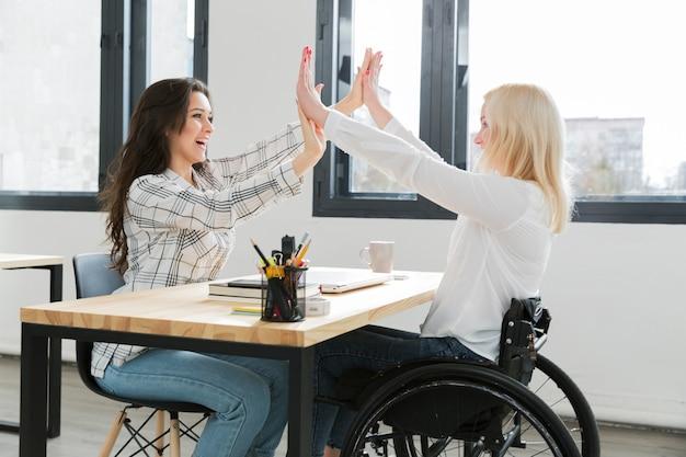 Vrouw in rolstoel high-fiving met haar collega