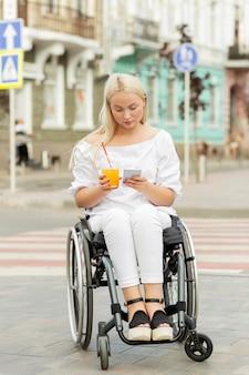 Vrouw in rolstoel met behulp van smartphone onder het genot van een drankje