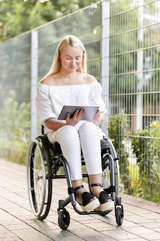 Vrouw in rolstoel met behulp van tablet