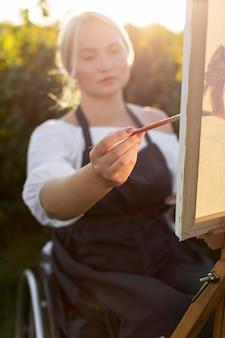 Vrouw in rolstoel met canvas en palet buitenshuis