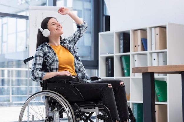 Vrouw in rolstoel met koptelefoon