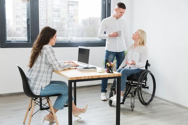 Vrouw in rolstoel op het kantoor met medewerkers