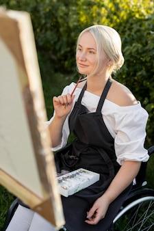 Vrouw in rolstoel schilderen op canvas in de natuur