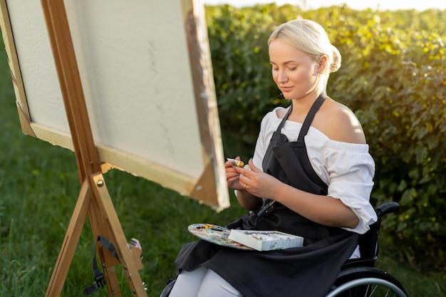 Vrouw in rolstoel schilderij in de natuur