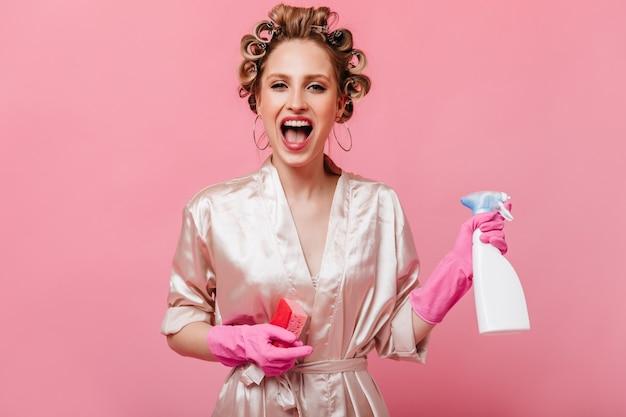 Vrouw in ronde oorbellen, haarkrulspelden en peignoir houdt wasmiddel vast
