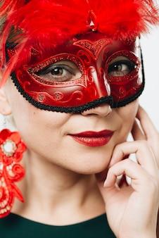 Vrouw in rood carnaval-masker met veer