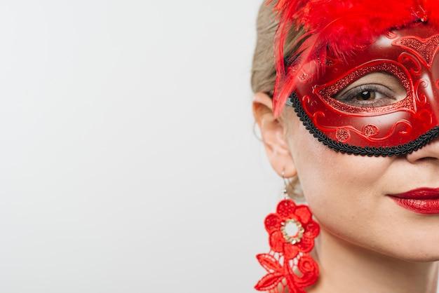 Vrouw in rood carnaval-masker