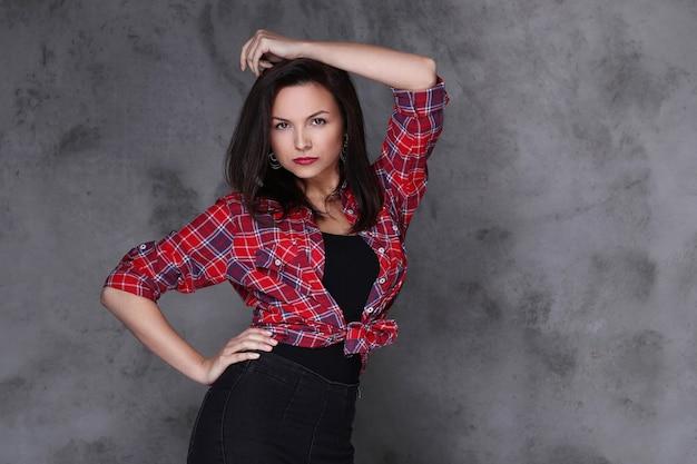 Vrouw in rood geruit overhemd en zwarte jeans