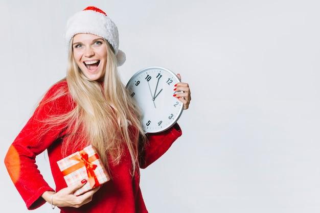 Vrouw in rood met klok en geschenkdoos
