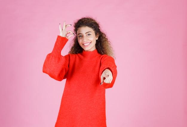 Vrouw in rood overhemd die iemand vooruit opmerkt en positieve energie verzendt.