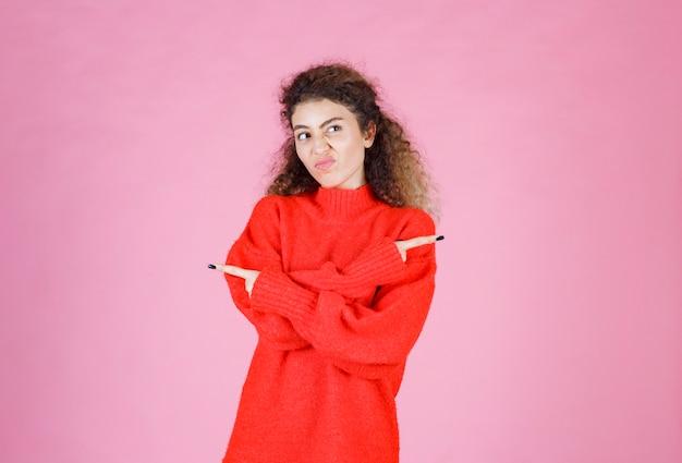 Vrouw in rood overhemd wijzend op iets aan de rechterkant.