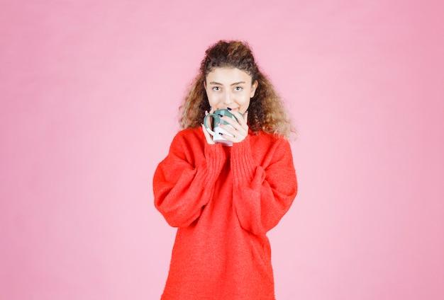 Vrouw in rood shirt drinken van een kopje koffie.
